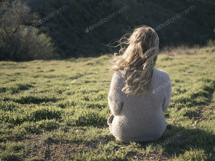 Young woman with windblown hair sitting on a hillside looking out toward the sun