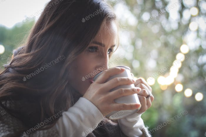young woman drinking hot coffee on a cold morning