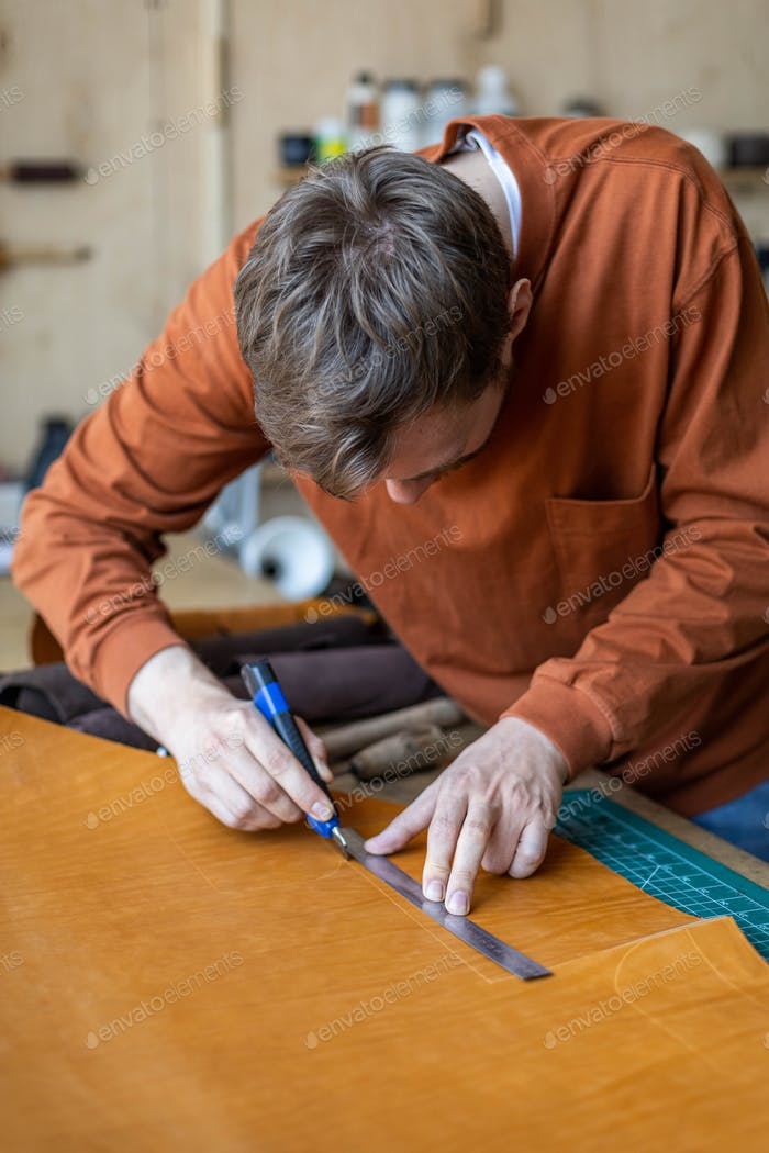 Male tanner making cutting scheme of bag working at leather workshop. Handcrafted creating
