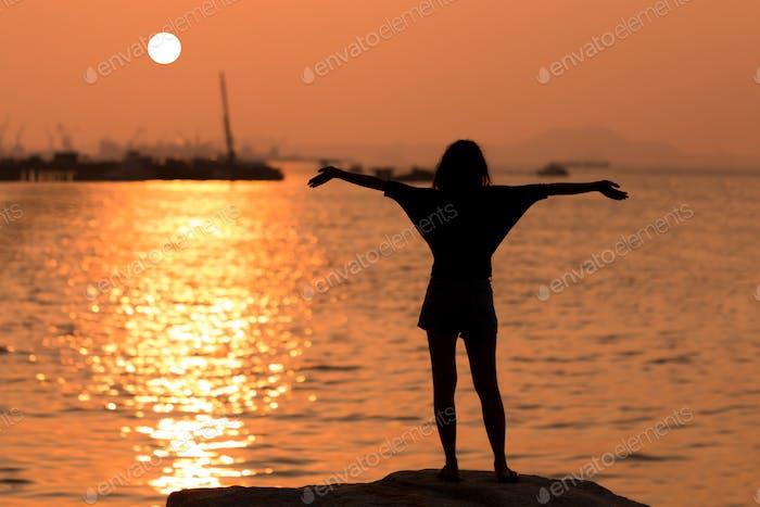 Silhouette der Frau steht auf dem Felsen mit ausgestreckten Armen und beobachtete den Sonnenuntergang am