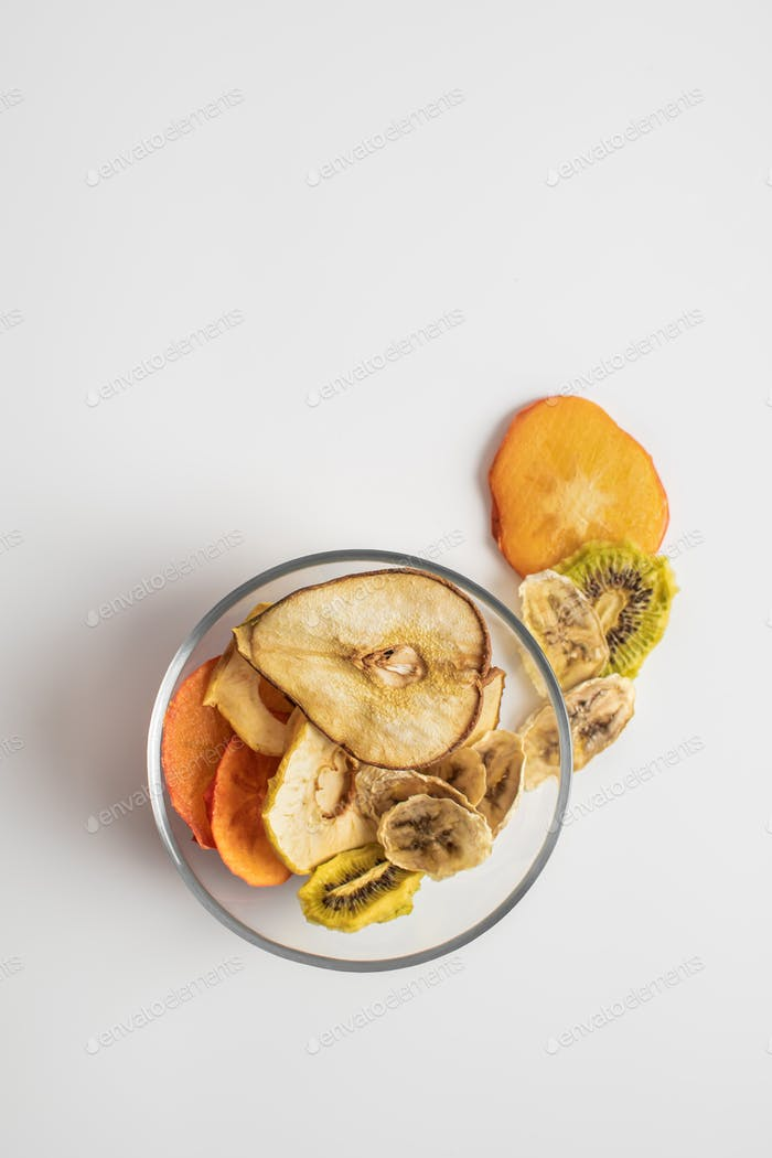 Dehydrated fruits in the plate on a light background.