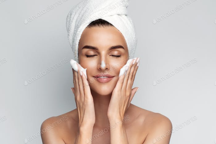 Glückliche Frau mit Badetuch auf dem Kopf kümmert sich um das Gesicht der Haut, trägt Reinigungsschaum nach Sho auf