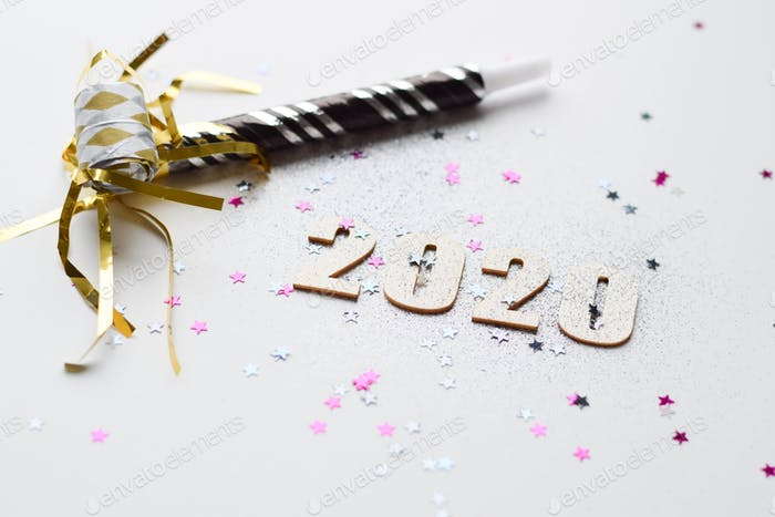 Happy New Year 2020 with glitter and pink and silver star sprinkles and party favors