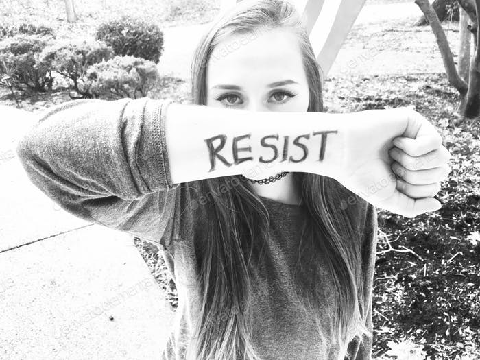 Resist. Activism, young woman with word written on her arm, silent protest. High key black and white