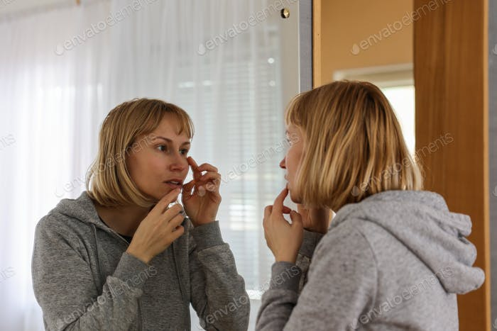 A woman looks at herself in the mirror in the room