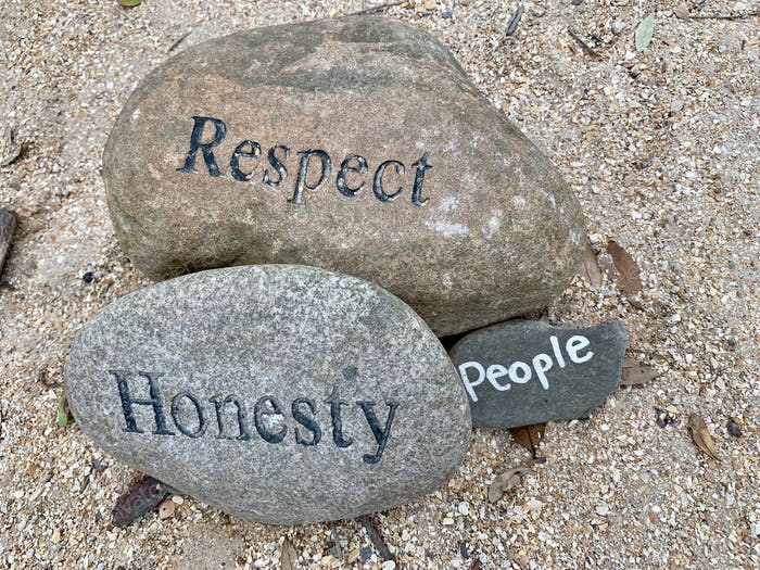 Three stones or rocks sitting in a garden with the words respect, honesty, and people