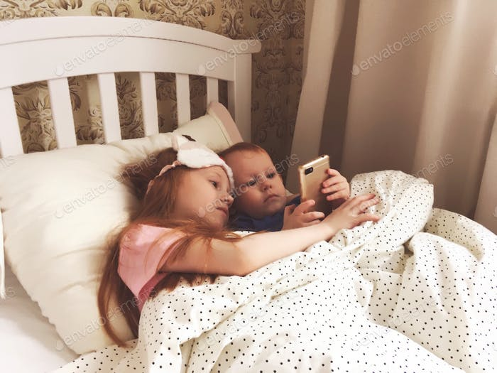 Children lie in Bed and use a gadget, use of a gadget, Children use a mobile phone, bedroom, white b
