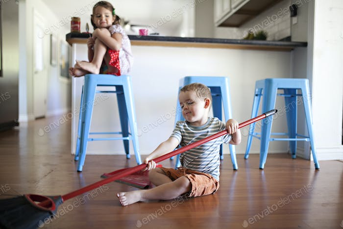 toddler with broom tormenting his sister at home in the kitchen