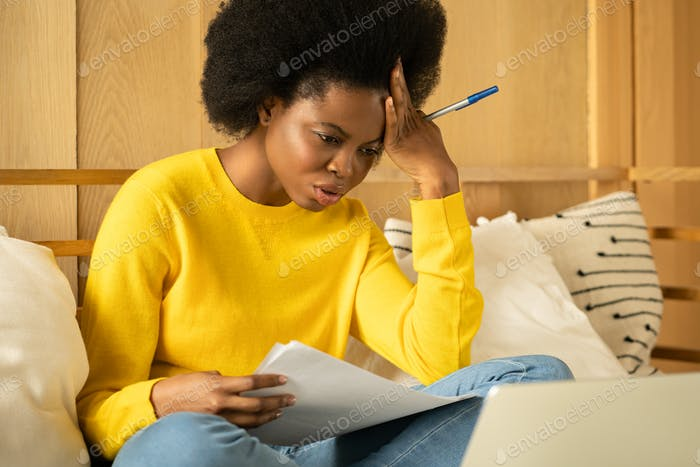 Unhappy Black woman reading negative news from bank about debt or eviction notice, bankruptcy