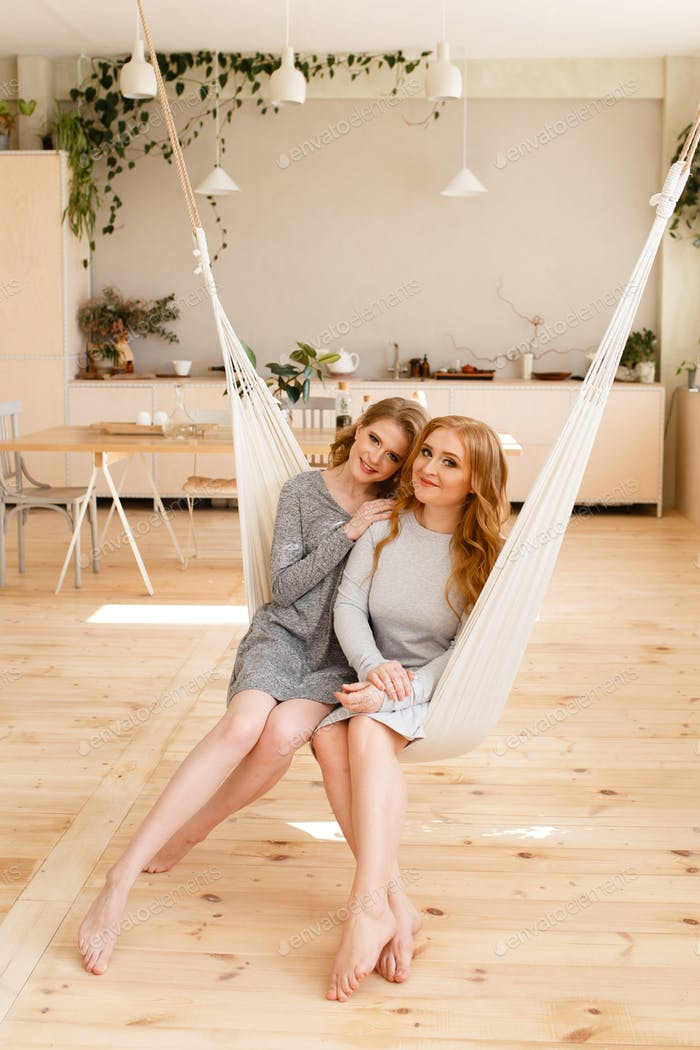 Two happy cute curly adult sisters of a blonde girlfriend in home clothes hug