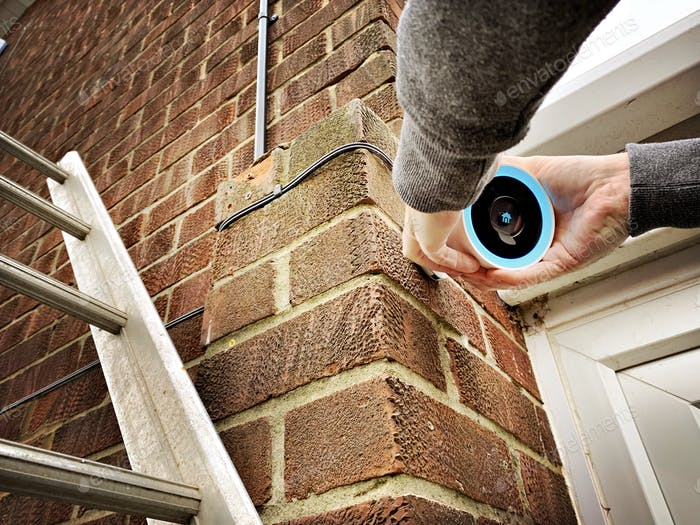 Low angle view of a person on ladders fitting a Google Nest CCTV home security camera. Modern tech