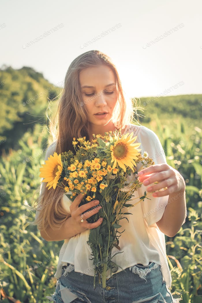 Slow Living concept New Lifestyle Trend. Relaxing young woman with lowers in nature, in corn, sunflo
