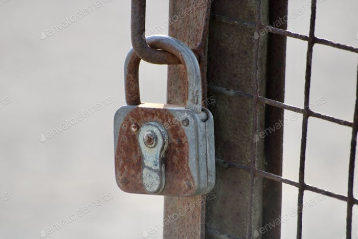 Rusty lock on a rusty fence