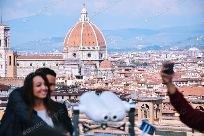 A blurry young couple in love tourists taking a selfie with a selfie stick