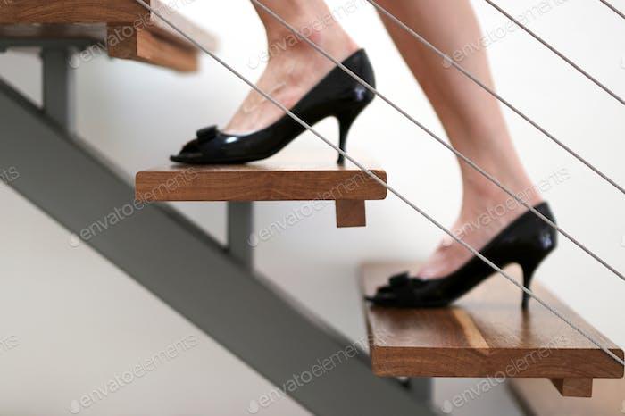 Berufstätige Frau, die mit schwarzen Pumps aus schwarzem Lackleder die Metall- und Holztreppe hinaufgeht