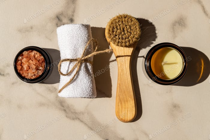 Natural cosmetics set in eco-friendly packaging on a marble table with ctton flower and towel. SPA,