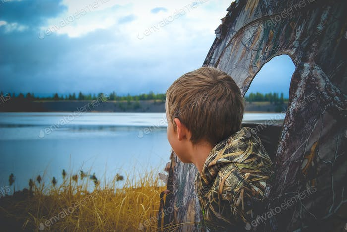 Young boy looking out of a blind at duck decoys