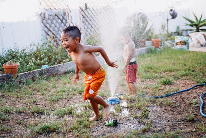 Two diverse young little brothers brother playing outside backyard summer with hose sprinkler home f