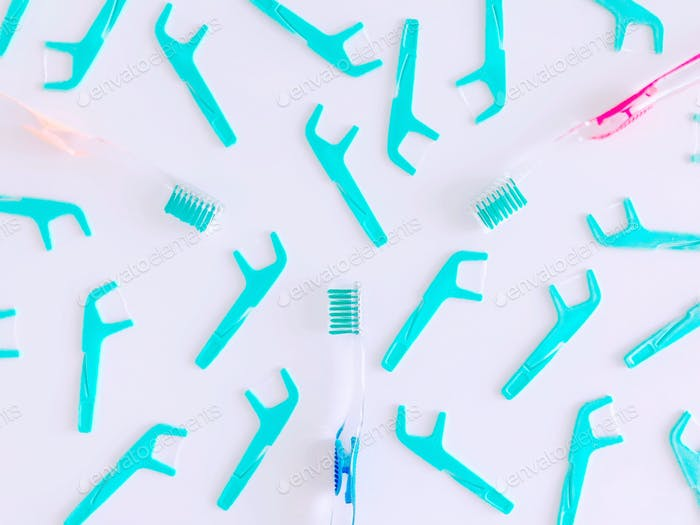 Green floss & toothbrushes flat lay. Brushing & flossing is very important for healthy teeth & body