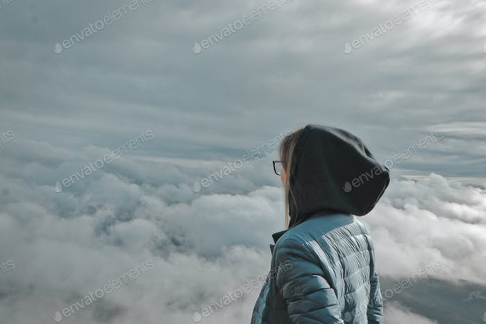 A woman stands backwards and watches the cloudscape
