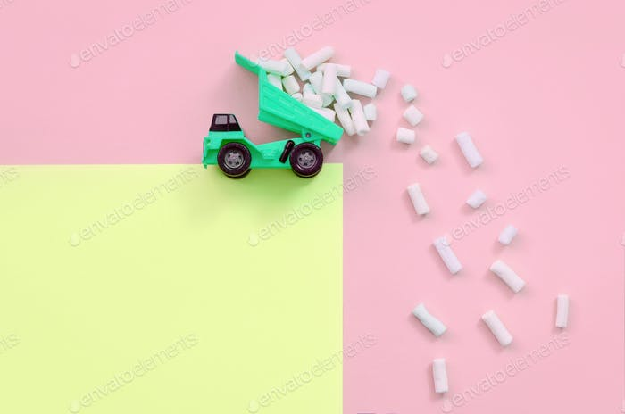 Green little toy dump truck throws marshmallow pieces from its raised back on a pastel yellow and