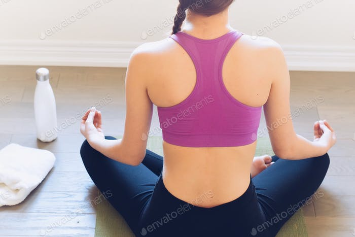 Young woman sitting in a crossed legged yoga position