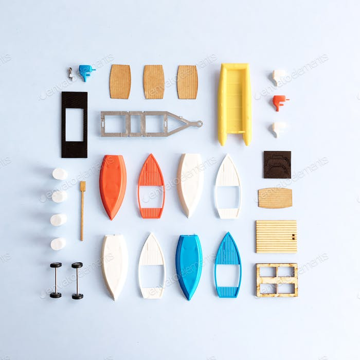 Looking down at a flat lay of primary color model boat pieces on a powder blue background.