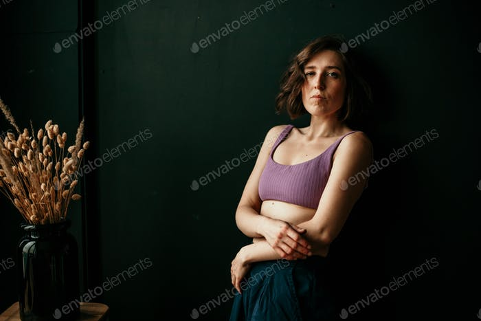 portrait of a beautiful young serious woman with freckles and wavy hair bob hairstyle in a lilac top