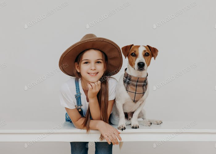 Content pretty girl wears hat, leans at white table, poses near pedigree dog