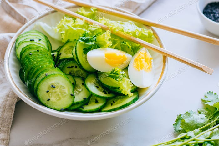 Healthy bowl, cucumber salad with eggs and coriander on marble background