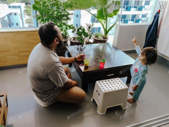 padre y niño pequeño en el balcón. hora de la comida