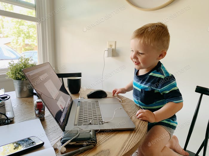 Young boy sits at the computer doing distance learning and home school.