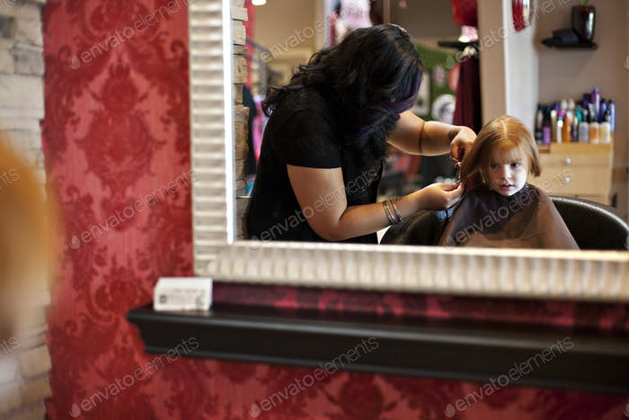 Mädchen bekommt einen Haarschnitt.