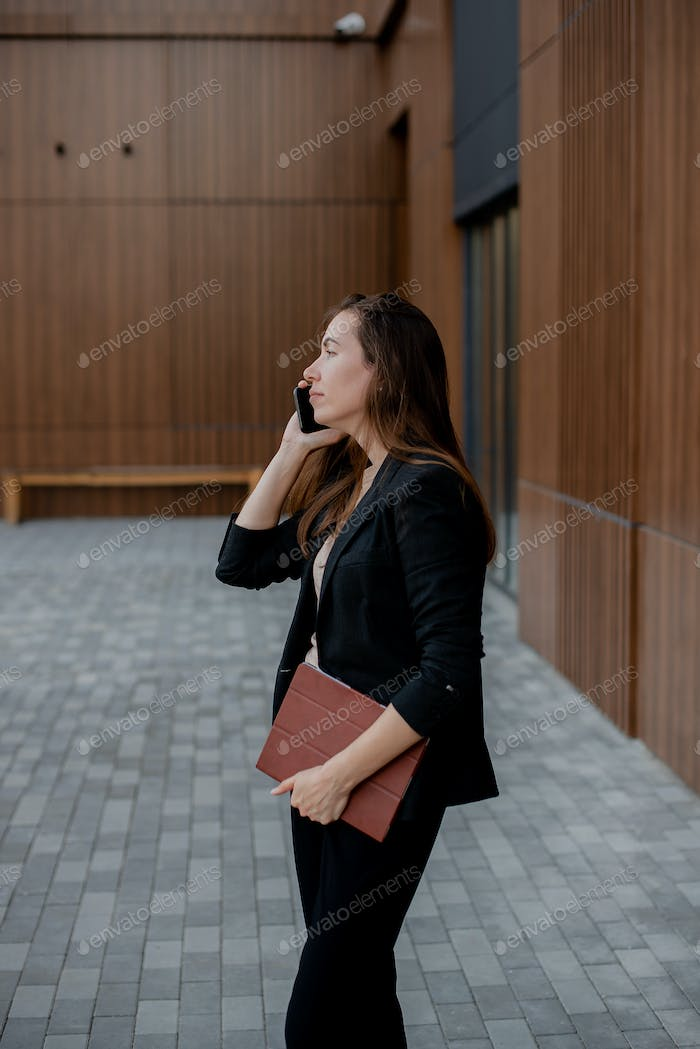 Young woman in a suit talking on the phone near a modern office building with a tablet in her hands