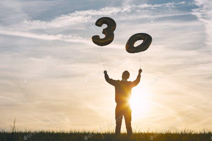 El hombre celebra treinta años de cumpleaños. Persona que sostiene globos de helio en forma del número 30 al atardecer