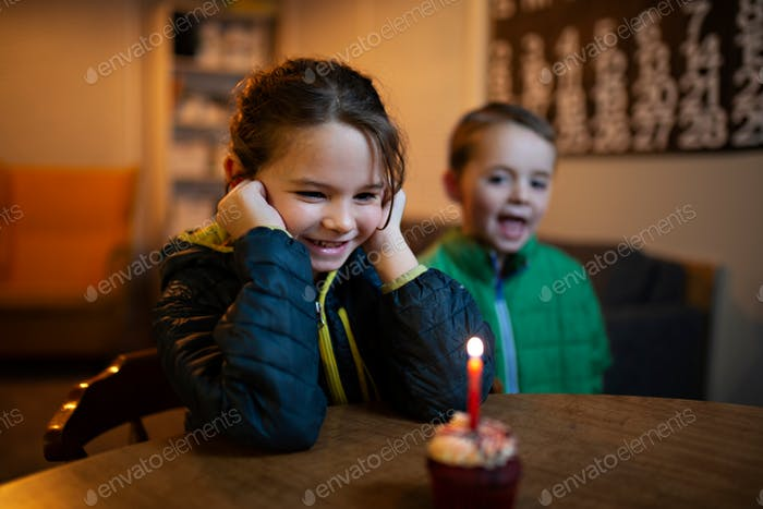 happy little girl blowing out birthday candles