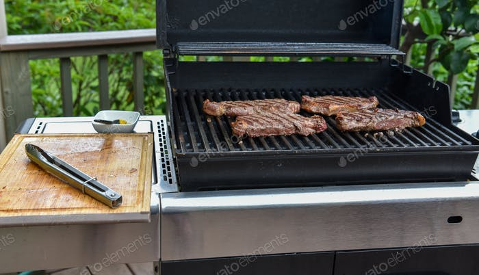 Perfectly seared New York strip steaks on the grill.