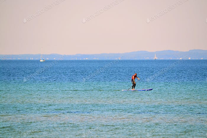 Seascape with a man paddleboarding