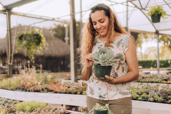 Smiling woman business owner holding succulent plant in plant nursery or garden center