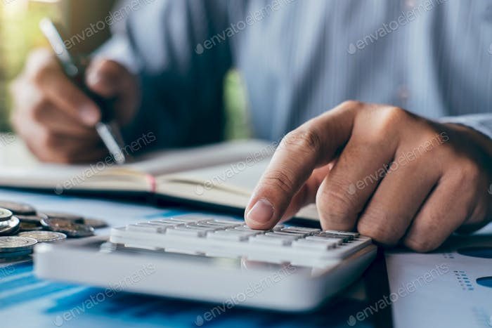 Businessman accountant making notes at report doing finances and calculate about cost of investment
