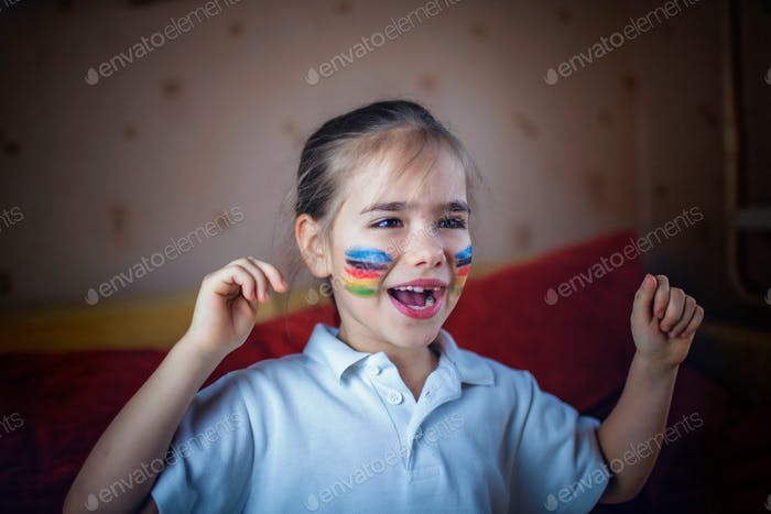 Cute young sport fan with colored cheeks sitting on sofa, watching sport games and cheering for her