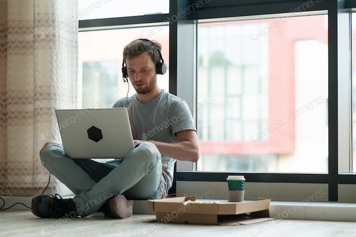 Adult man programmer working from home using laptop and headphones. Creative Home office