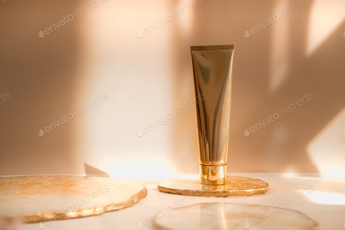Cosmetic gold tube with on pastel background. Beauty product still life commercial ad photography.