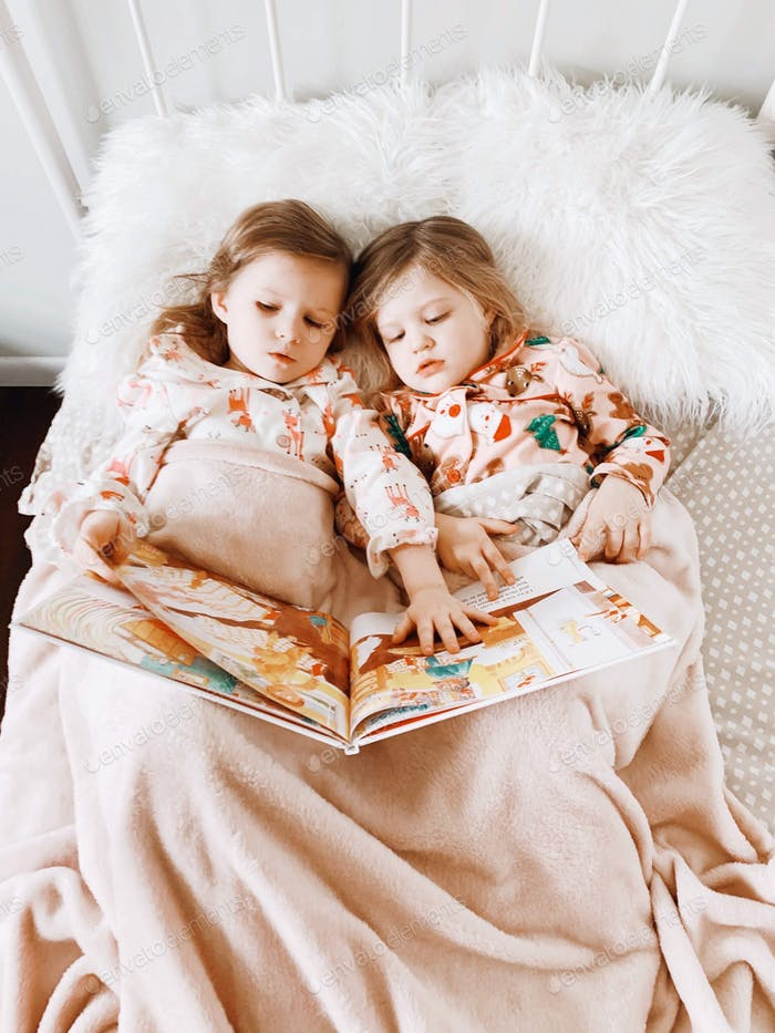 Two little girls are laying in bed in their Christmas pajamas reading a book together. They are cove