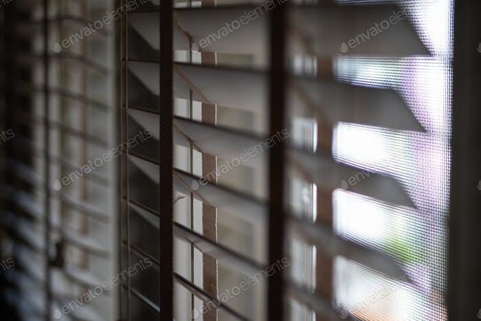 Timber venetian blinds on window casting shadows