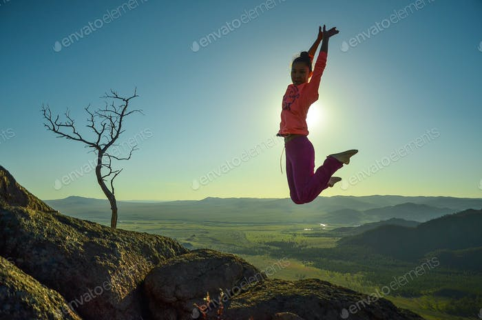 Jumping girl covering the sun