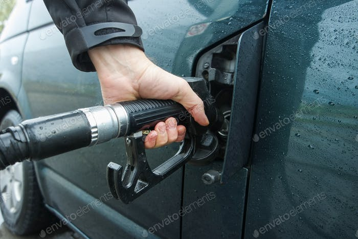 Close up of man's hand holding fuel pump and refueling car.