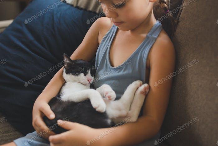 Little girl holding her sleeping kitten