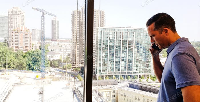 Millenial businessman on his cellphone looking through the window at the Atlanta skyline...