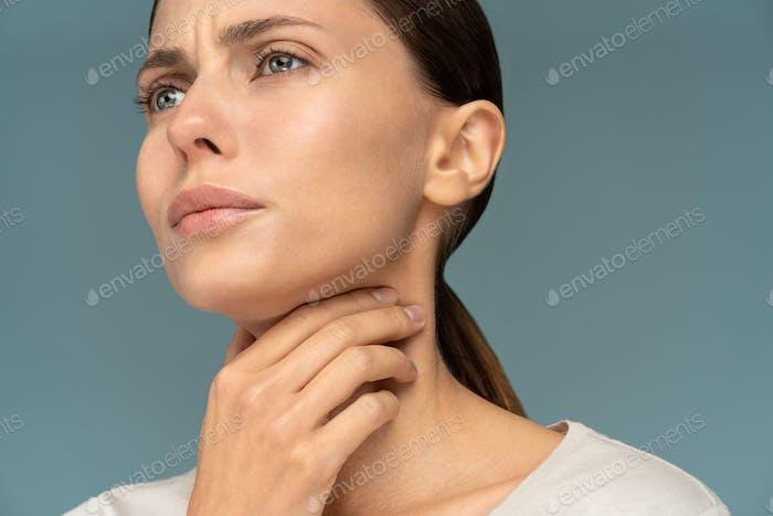 Frau mit Halsschmerzen, Mandelentzündung, fühlt sich krank, erkältet, leidet unter schmerzhaftem Schlucken